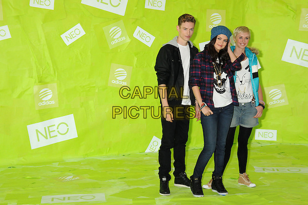 Selena Gomez (centre) & models .Adidas NEO Label Signs Selena Gomez as New Style Icon and Designer held at 1745 E 7th Street, Los Angeles, California, USA..November 20th, 2012.full length blue knitted beanie hat red lumberjack shirt check white shirt black skull print jeans denim trainers sneakers  jacket turquoise puffa sleeveless shorts tights .CAP/ADM/BP.©Byron Purvis/AdMedia/Capital Pictures.