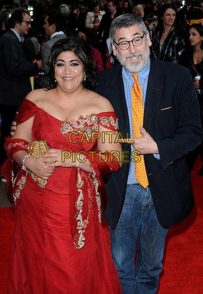 "GURINDER CHADHA & JOHN LANDIS.The ""It's A Wonderful Afterlife"" UK premiere, Odeon West End, Leicester Square, London, England. .April 12th, 2010.half 3/4 length red dress gown off the shoulder gold silver trim detail clutch bag cleavage beard facial hair glasses orange tie blue shirt suit jacket hand pointing jeans denim.CAP/CAN.©Can Nguyen/Capital Pictures."