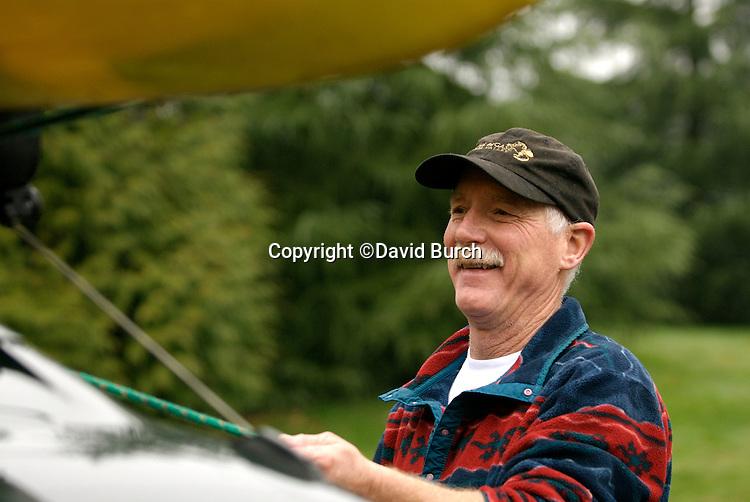 Mature man tying kayak on car, smiling