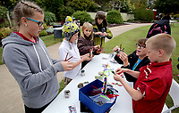 NWA Democrat-Gazette/DAVID GOTTSCHALK  Maria Sulzen (from left), 14, makes Magazine Butterflies Tuesday, October 10, 2017, with her brother Nathaniel, 12, Mary-Elizabeth, 8, Pauline-Mary, 11, Caitlyn Spaulding, education assistant, and brother Syril, 10, at the Botanical Garden of the Ozarks in Fayetteville during the Garden's 10 Birthday Party. The party included free entry, crafts, entertainment and ten percent off memberships.