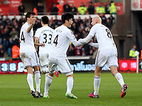 SWANSEA, WALES - FEBRUARY 07: Ki Sung Yueng of Swansea (C) celebrates his equaliser with Jonjo Shelvey (R) during the Premier League match between Swansea City and Sunderland AFC at Liberty Stadium on February 7, 2015 in Swansea, Wales.