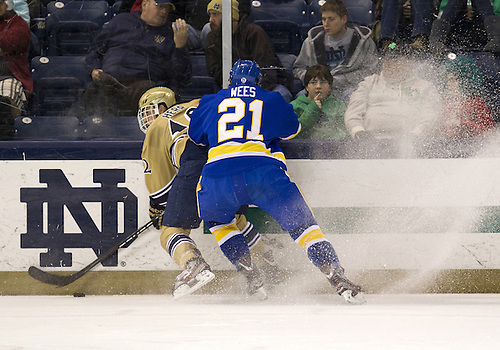 December 01, 2012:  Notre Dame left wing Sam Herr (#12) and Lake Superior State defenseman T.J. Wees (#21) battle along the boards during NCAA Hockey game action between the Notre Dame Fighting Irish and the Lake Superior State Lakers at Compton Family Ice Arena in South Bend, Indiana.  Notre Dame defeated Lake Superior State 6-1.