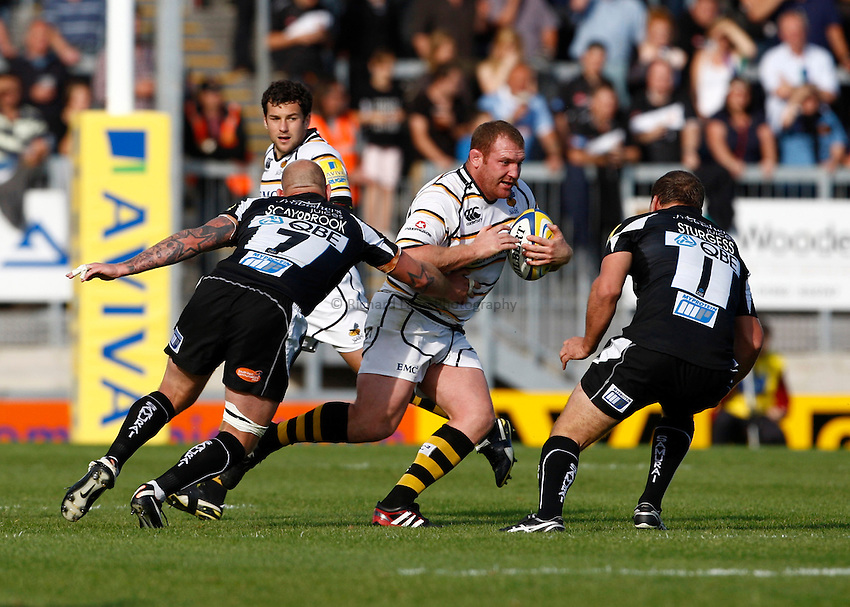 Photo: Richard Lane/Richard Lane Photography. Exeter Chiefs v London Wasps. Aviva Premiership. 25/09/2011. Wasps' Tim Payne is tackled by Exeter's Brett Sturgess and James Scaysbrook.