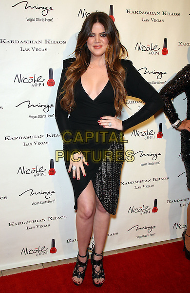Khloe Kardashian Odom .The Kardashian Family celebrates the Grand Opening of Kardashian Khaos at The Mirage Hotel and Casino, Las Vegas, Nevada, USA,.15th December 2011..full length hand on hip  black tulip wrap dress sandals heels shoes  open toe .CAP/ADM/MJT.© MJT/AdMedia/Capital Pictures.