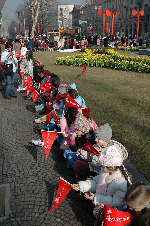 Bambini in attesa del passaggio della fiaccola olimpica di Torino 2006. Children waiting the olympic torch of Torino 2006.
