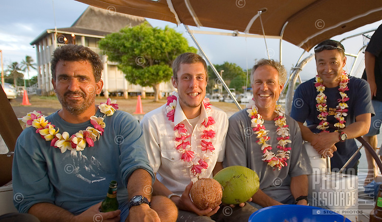 Happy crew of a sailboat with leis in Haleiwa, Hawaii, after accomplishing a successful Pacific crossing