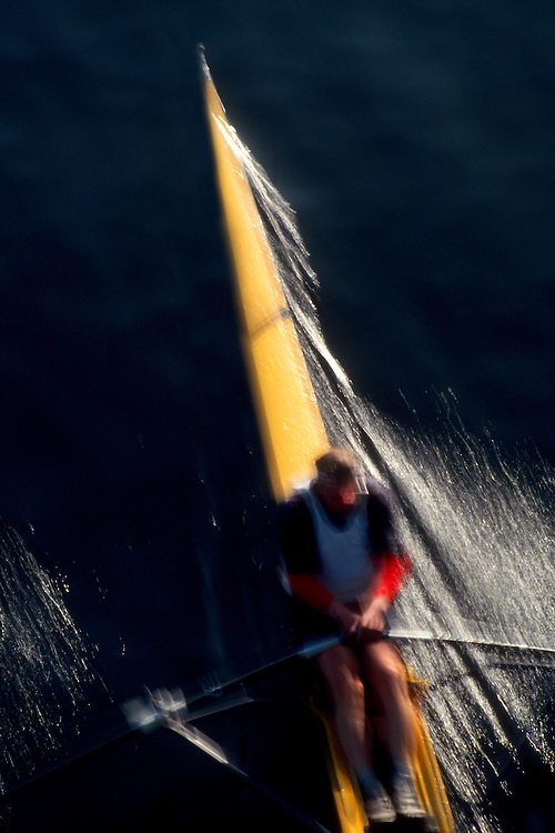 Man rowing single racing shell in blur motion from above.
