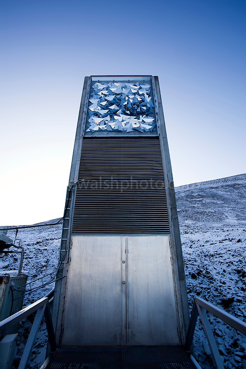 """Limited edition C-Type Prints available - contact me for more details.<br /> <br /> Nestled into the rocky waste of plataberget Mountain about Svalbard's airport, the Global Seed Vault is at once startling and innocuous. Designed by architect Peter W. Søderman at Barlindhaug Consulting, this concrete, steel and glass structure is the first layer of security to a repository of millions of seeds from around the world, stored here in case of disaster, disease, or war...The Svalbard Global Seed Bank is situated 120 metres (390 ft) inside a sandstone.mountain at Longyearbyen on Spitsbergen Island, in the Svalbard archipelago about 1300km from the North Pole. Svalbard was considered ideal for the bank, due to low tectonic activity and its permafrost, which will aid preservation. Even if sea levels rise due to climate change - and the melting of ice caps, the seeds will be safe and dry , as they are stored at a location 130 metres (430 ft) above sea level. ..The Svalbard Global Seed Vault  provides a safety net against accidental loss of diversity from traditional storage within genebanks around the world, and has a capacity for 4.5 million seeds. Although the media has made much of the """"Doomsday Vault's"""" role in providing security in the face of war or or catastrophe, the operators - the Norwegian government  and the Global Crop Diversity Trust and the Nordic Genetic Resource Center - say that it will be most useful when genebanks lose samples due to mismanagement, accident, equipment failures, funding cuts and natural disasters."""