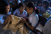 Students at Kartini Emergency School taking part in the dress making class. Acquiring practical skills is an important part of the education programme. Since the early 1990s, twin sisters Sri Rosyati (known as Rossy) and Sri Irianingsih (known as Rian) have used their family inheritance to set up and run 64 schools in different parts of Indonesia, providing primary education combined with practical skills to some of the country's most deprived children.