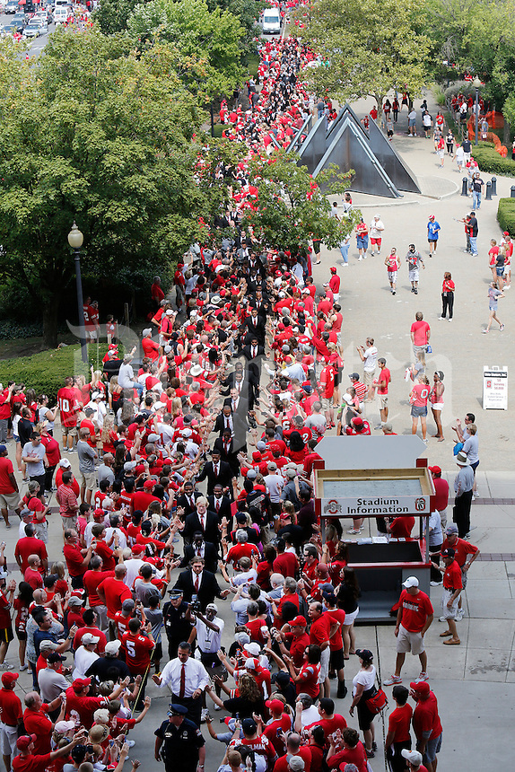 Ohio State head football coach Urban Meyer (bottom, white shirt) leads his team into the stadium before the start of a football game between the Ohio State Buckeyes and the San Diego State Aztecs on Sept. 7, 2013 at Ohio Stadium. (Columbus Dispatch photo by Fred Squillante)