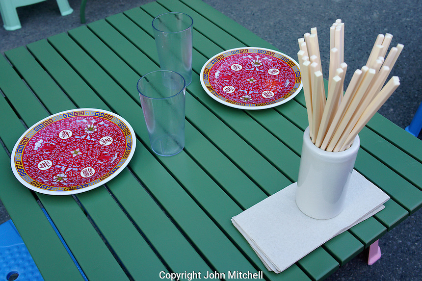 Chinese plates and chop sticks  in an outdoor restaurant at the night market in Chinatown, British Columbia, Canada