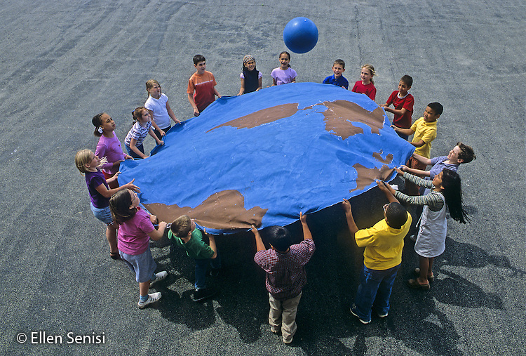 "MR / Schenectady, New York. Yates Arts Magnet School. 3rd grade students (some with special needs) play ""earth ball"" game which requires them to work together to bounce ball. (Images of students painting this cloth are also available. Project is an example of integrated curriculum in arts magnet school; in this case, social studies, art, and physical education are combined.) MR: LC-gr3 Originally listed as PN-31028. ©Ellen B. Senisi MR: L-C original on slide film ©Ellen B. Senisi"