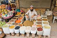 A photo of a muslim man selling grains in the old bazaar in Rawalpindi in Pakistan