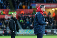 (L-R) Manchester City manager Pep Guardiola and Swansea manager Paul Clement watch the game from the touch line during the Premier League match between Swansea City and Manchester City at The Liberty Stadium, Swansea, Wales, UK. Wednesday 13 December 2017
