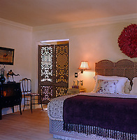 A guest bedroom uses a screen as a headboard and another ornamental screen as a door