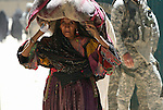 A woman from the nomadic Kuchi tribe leaves the district center of Shar-e-Safa in Zabul province, Afghanistan. U.S. troops provided medical care, and Afghan police distributed winter clothes, food staples and other relief items to about 200 people before they ran out of supplies.  Aug. 25, 2008. DREW BROWN/STARS AND STRIPES