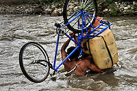 A contraband smuggler carries gasoline barrels on a bicycle through the river Tachira on the Colombia-Venezuela border, 3 May 2006. Venezuelan gasoline, being 20 times cheaper than in Colombia, is the most wanted smuggling item, followed by food and car parts, while reputable Colombian clothing flow to Venezuela. There are about 25,000 barrels of gasoline crossing illegally the Venezuelan border every day. The risky contraband smuggling, especially during the rainy season when the river rises, makes a living to hundreds of poor families in communities on both sides of the frontier.