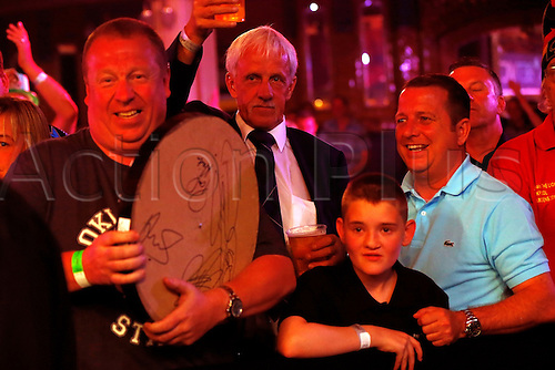 23.07.2016. Empress Ballroom, Blackpool, England. BetVictor World Matchplay Darts. Phil Taylor signs a dart board after the game and presents it to a young supporter