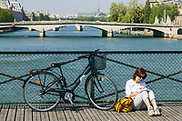 Woman sitting and writing on the Pont des Arts next to her bicycle, with the Seine and Pont du Carrousel to the south, Paris, France