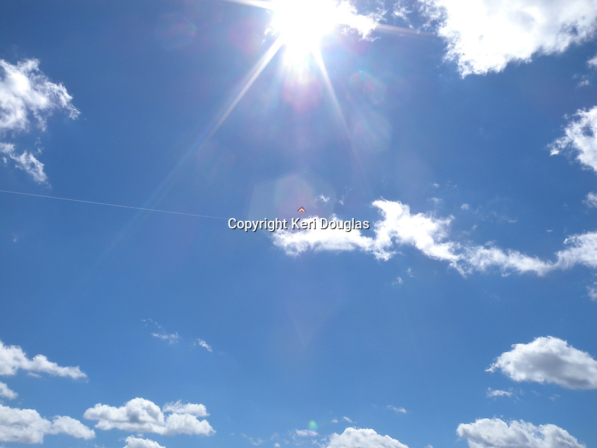 Kite in the sky filled with clouds. Bright blue, Sun burst.