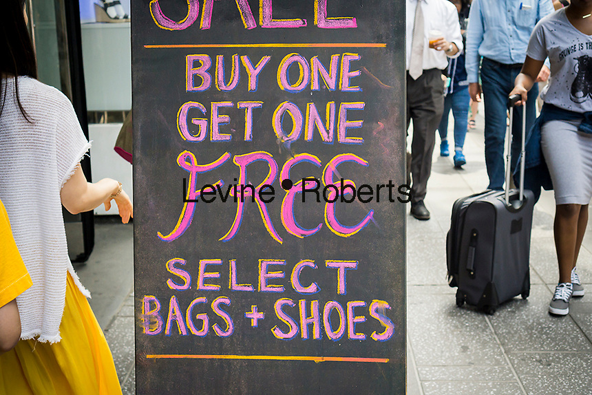 """A """"buy one, get one"""" promotion advertised outside of a clothing store in New York on Friday, June 17, 2016.  (© Richard B. Levine)"""