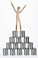 Winner mannequin on top of tin cans pyramid (Licence this image exclusively with Getty: http://www.gettyimages.com/detail/102170463 )
