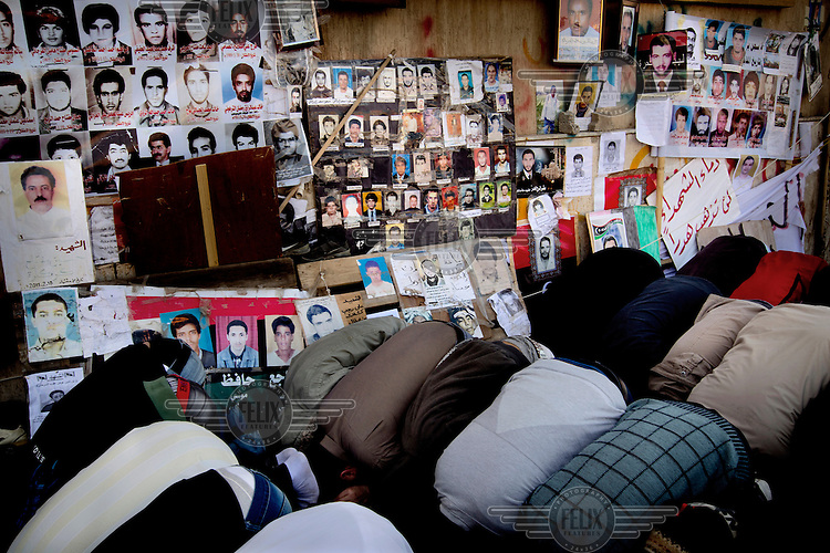 Men kneel down at Friday prayers in Benghazi, next to pictures of missing people. On 17 February 2011 Libya saw the beginnings of a revolution against the 41 year regime of Col Muammar Gaddafi.