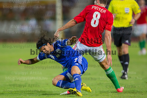 Israel's Lior Refaelov (L) falls as he fights for the ball with Hungary's Adam Pinter (R) during a friendly football match Hungary playing against Israel in Budapest, Hungary on August 15, 2012. ATTILA VOLGYI