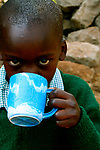 A student enjoys his morning Uji Break at the Hamomi Children's Center in Nairobi, Kenya