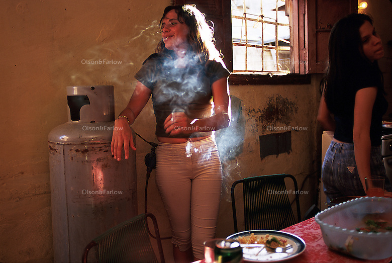 Ariadna Del Carmen Rodriguez--Single girl in the Cuban Underground. Ariadna smokes in the kitchen before a party with friends begins.  She is a young woman trying to lead an independent life and follow her dreams. Working as an actress in the theater, her charm is a mixture of innocence and a theatrical personality. She lives with a roommate in the city of Havana while she is going to school. She and her room mate are both actresses and wander through the academic and Cuban underground of artists and friends.
