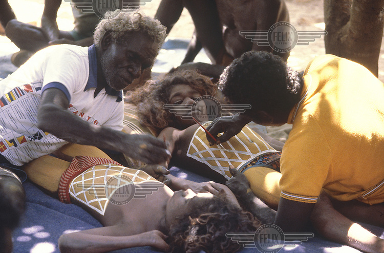 © Penny Tweedie / Panos Pictures..Aborigines, Arnhemland, AUSTRALIA..Madawilli and Bulun Bulun being painted with their clan totemic symbol, sugar-bag dreaming, for their initiation ceremony.