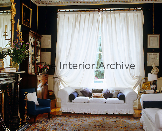 The blue drawing room has a generous drape of white linen across the window
