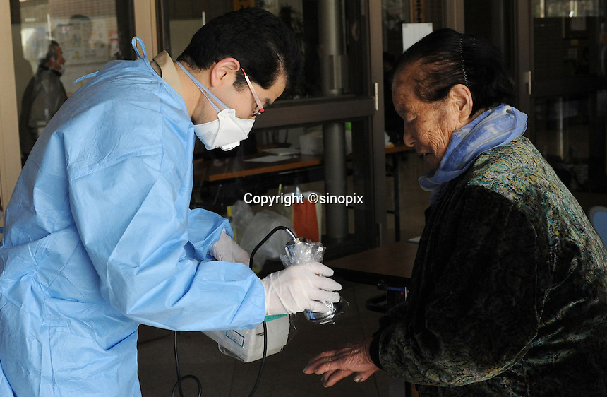 A old lady is tested for radiation in Fukushima City, Japan, 60 km from .the Fukushima Daiichi Nuclear Power Plant and with-in the 80 km exclusion zone.  The nuclear Plant was damaged during the  Earthquake and following Tsunami that struck Japan 11th March 2011..17 Mar 2011