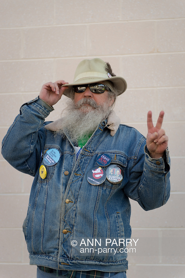 """Merrick, New York, USA. October 23, 2016. FRED S. CHANDLER, 66, of North Bellmore, wears political campaign buttons supporting Democratic presidential candidate Hillary Clinton, and holds two fingers up to make a Peace Sign or """"V for Victory"""" sign, while attending rally to demand public water and stop New York American Water (NYAW) rate hike. On denim jacket were buttons for Hofstra University DEBATE 2016 - and """"So My Daughter Knows She Can Be President. Hillary 16"""" - """"TRUMPBUSTERS"""" - """"CLINTON KAINE 16"""" - and Monopoly Man character with """"NEVER TRUMP"""" text."""