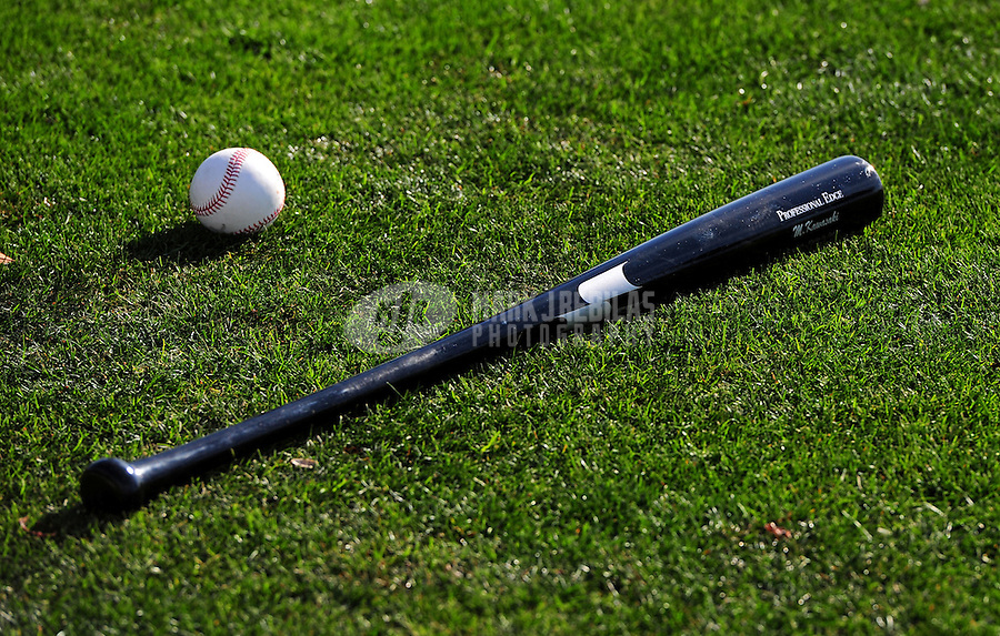 Feb. 15, 2012; Peoria, AZ, USA; A baseball and bat sit in the grass on the field during a Seattle Mariners pitchers and catchers workout at the Peoria Sports Complex.  Mandatory Credit: Mark J. Rebilas-.