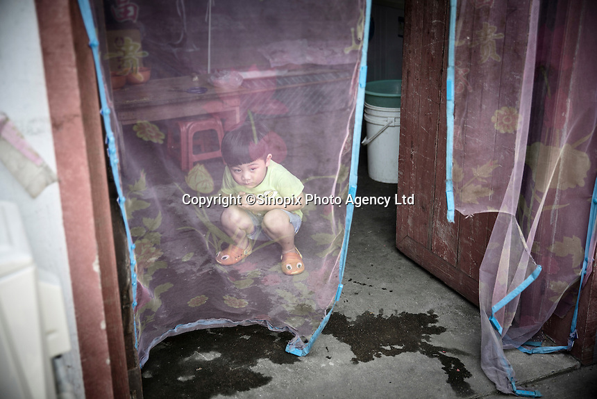A young child peeks out of a door in Xingxing village on the outskirts of Shanghai,  China on 14 August 2015.  As China's sputtering economy has beginning to affect employment, many migrants who used to live in the village to work on Shanghai's numerous construction sites and factories are beginning to thin out.