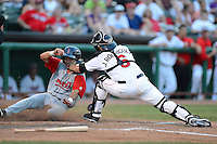 Tri-City ValleyCats catcher Jake Rodriguez (6) tags out Carlos Asuaje (15) sliding into home during a game against the Lowell Spinners on July 5, 2013 at Joseph L. Bruno Stadium in Troy, New York.  Tri-City defeated Lowell 5-4.  (Mike Janes/Four Seam Images)