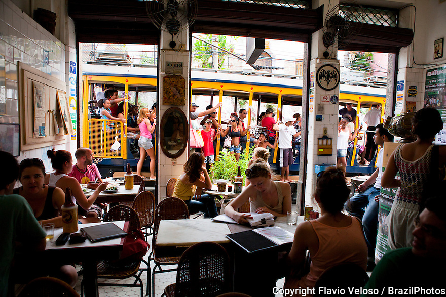Young people drink beer at Bar do Mineiro in Santa Teresa quarter, a bohemian district in Rio de Janeiro,  Santa Teresa streetcar in background, Brazil.