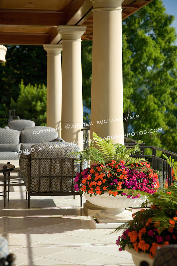 a garden pot made by Longshadow is filled with a lush green fern and colorful annuals on this sunny, covered patio lined with luxurious furniture.  Design by Sander Groves Landscapes, Inc., and Linda Attaway Landscape Architect.