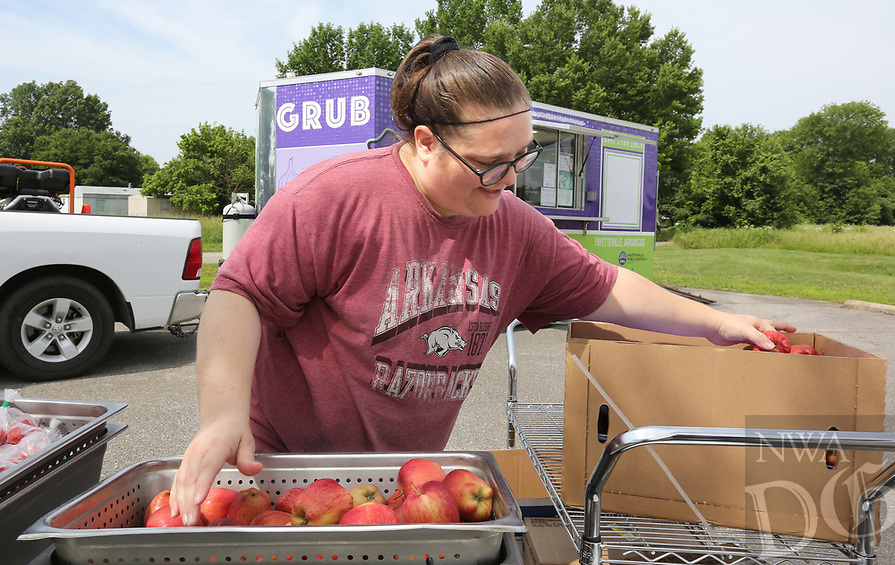 NWA Democrat-Gazette/DAVID GOTTSCHALK Sheri Clayton, food manager at Ramay Junior High School, sets up the apples and cherry tomatoes Monday, June 3, 2019, in front of the Fayetteville Public Schools' Purple Dog Food Truck at the Shelton Tucker Craft American Legion Post 27 on Curtis Avenue in Fayetteville. The American Legion location is the new third location for the food truck that will provide a lunch to those 18 years and younger. Local school districts begin their free summer food service programs for kids this week.