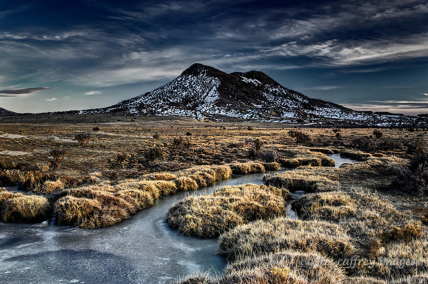 Cerro Cuate in the Rio Puerco Valley in the San Juan Basin of northwestern New Mexico with an iced over stream at twilight in mid winter.
