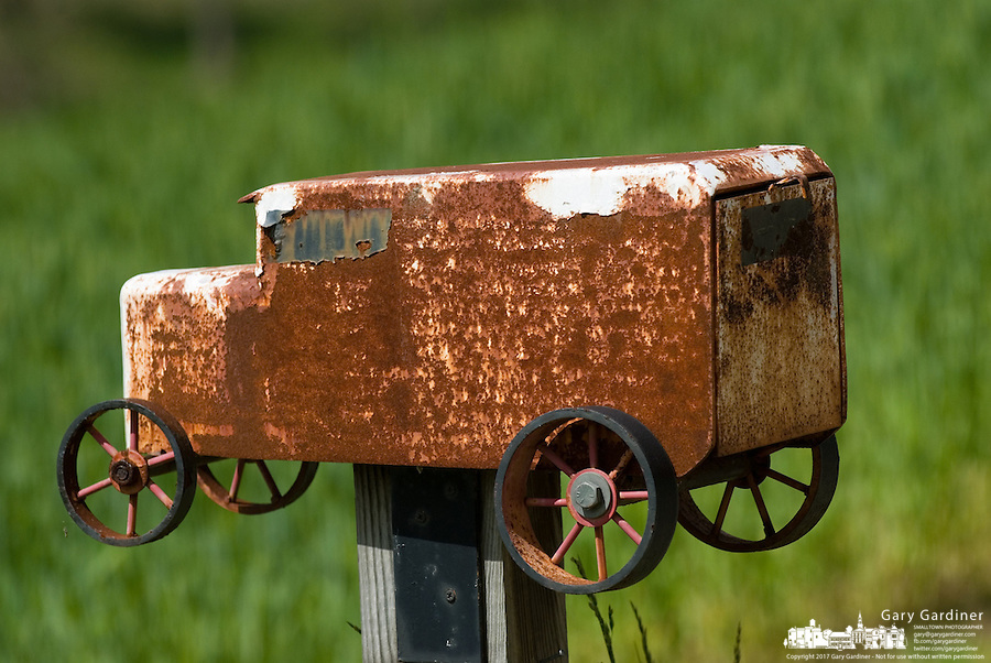 A rusted mailbox resembling a utility van truck marks a field of wheat and the entrance to a farm near Granville, OH.<br />