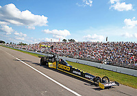 Aug 15, 2014; Brainerd, MN, USA; NHRA top fuel dragster driver Richie Crampton being towed back to the pits past fans in the grandstands during qualifying for the Lucas Oil Nationals at Brainerd International Raceway. Mandatory Credit: Mark J. Rebilas-