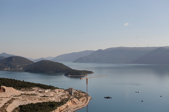 Die Baustelle der Pelješac-Brücke auf der Seite des kroatischen Dorfs Komarna. Die Bauarbeiten wurden Ende 2012 gestoppt. Die Brücke soll die Lücke im kroatischen Straßennetz schließen, damit Touristen in Zukunft nicht mehr auf der Adriaautobahn durch das bosnische Staatsgebiet bei Neum fahren müssen. Für den Ort Neum hätte dies unabsehbare wirtschaftliche Konsequenzen. / The Contrusction-site of the Pelješac-Bridge at the side of the Croatian village of Komarna. The construction was stopped at the end of 2012 but is thought to be continued as soon as new possibilities to finance the project are found out. The bridge should connect Croatian territory in the north and in the south of Neum. Travellers should have the opportunity to bypass Neum and the Bosnian territory in the future, while driving at the Adriatic-Highway.<br />