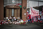 A woman attaching a scarf to the Shankly Gates next to the memorial at Anfield to the 1989 Hillsborough stadium disaster where 96 Liverpool football fans lost their lives. Mourners and well-wishers have been leaving flowers, scarves and wreaths after the publication of a report the previous week by the Hillsborough Independent Panel which released new information about the tragedy. The Hillsborough Justice Campaign had been campaigning for a new inquest into the disaster for the last 23 years. Photo by Colin McPherson.