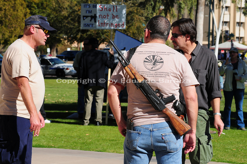 """Phoenix, Arizona. January 19, 2013 - A protester displays a rifle gun during Saturday's rally in Phoenix to oppose potential new laws that would limit access to guns and ammunition in the United States, among other regulations proposed. As President Barack Obama proposed new gun regulations last week, gun owners demonstrated against it with national """"Guns Across America"""" rallies to defend the Second Amendment. Dozens showed up at the Arizona State Capitol, many of them carrying weapons. Photo by Eduardo Barraza © 2013"""