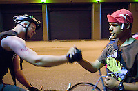 3 July 2005 - New York City, NY, USA - &quot;Junjun&quot; (R) salutes a rider arriving at an alleycat checkpoint on 43rd street in New York City, USA, July 3rd 2005. Alleycats are urban cycle races held informally - without notification of the authorities - on open roads and in real traffic, to simulate the messenger's working conditions. Photo Credit: David Brabyn<br />