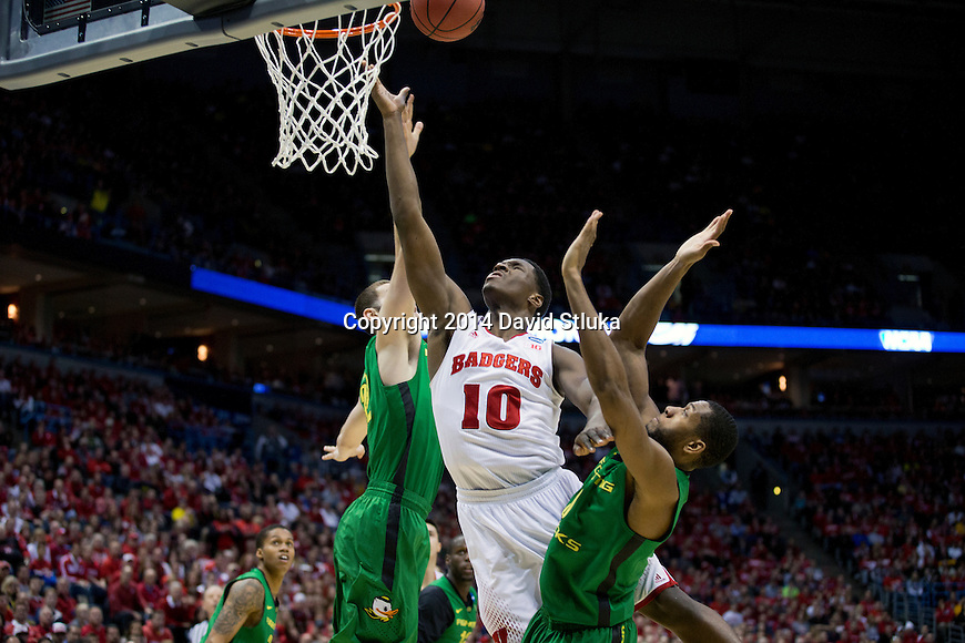 Wisconsin Badgers forward Nigel Hayes (10) shoots the ball over 2 defenders during the third-round game in the NCAA college basketball tournament against the Oregon Ducks Saturday, April 22, 2014 in Milwaukee. The Badgers won 85-77. (Photo by David Stluka)