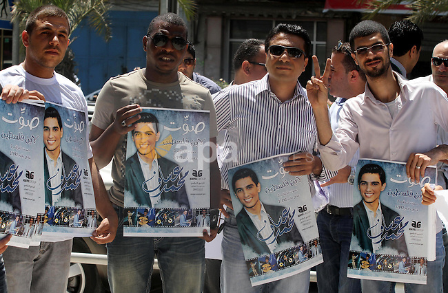 Palestinians hold pictures of Mohammed Assaf during a rally in solidarity with supporting the Palestinian ''Arab Idol'' star Mohammed Assaf in Gaza city on June 18, 2013. Since March, the handsome, immaculately dressed 23-year-old Gazan's powerful voice has propelled him every weekend to the ranks of only three remaining singers in a Beirut-based competition that started out with 27. Photo by Mohammed Asad