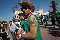 Los Angeles, CA -  Monday, June 23, 2014: A Mexico fan shows off his Mexico soccer national team tattoo while celebrating Mexico's victory over Croatia on the streets of downtown  Huntington Park.